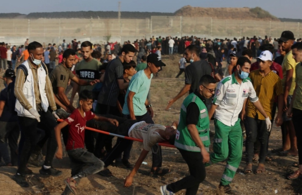 Palestinian medics in Gaza carry a wounded man during confrontations near the border fence with Israel on Saturday [Adel Hana/AP Photo]